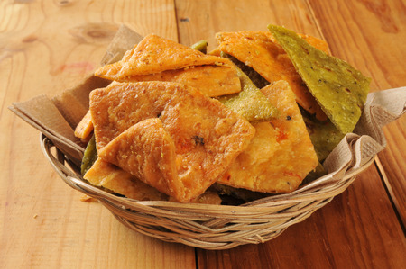 A basket of vegetable tortilla chips on a rustic wooden table