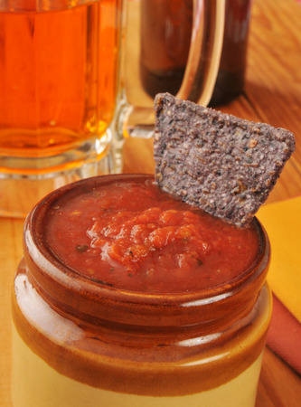 A blue corn tortilla chip in salsa with beer in the background