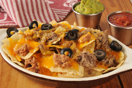 shreded: A dish of nachos with shreded beef, beans, cheddar cheese, guacamole and salsa