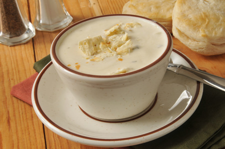 A cup of clam chowder with fresh baked biscuits