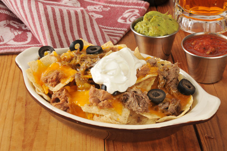 shreded: Nachos with shredded beef, cheese and beans and a mug of beer in the background