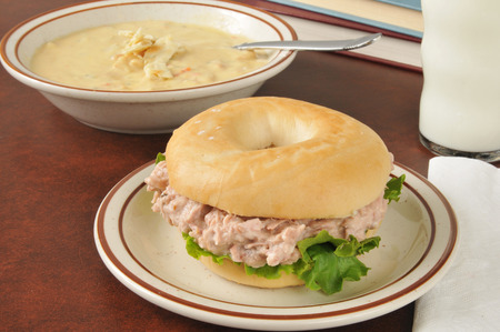 tunafish: Tuna sandwich on a bagel with a bowl of soup and schoolbooks