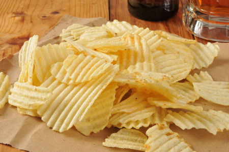 Wavy potato chips on brown paper with a mug of beer in the background