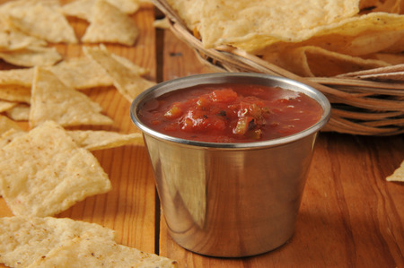 A dish of salsa and a basket of white corn tortilla chips