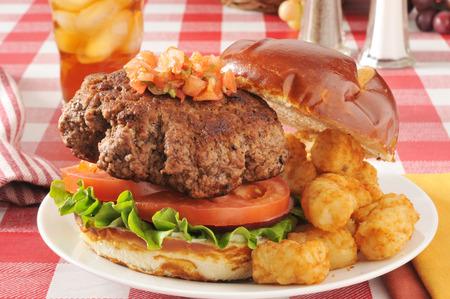 tots: a thhick hamburger on a pretzel bun with tater tots