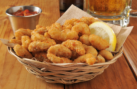 a basket of popcorn shrimp with lemon and cocktail sauce with a mug of beer 스톡 콘텐츠