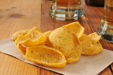 Corn chips and glasses of beer on a wooden bar counter photo