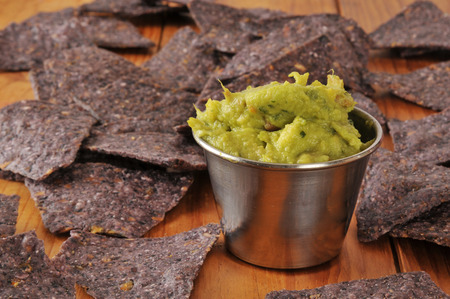 A serving of guacamole with blue corn tortilla chips