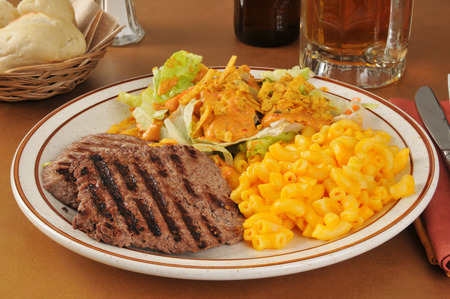 A cube steak dinner with macaroni and cheese and a salad Stok Fotoğraf