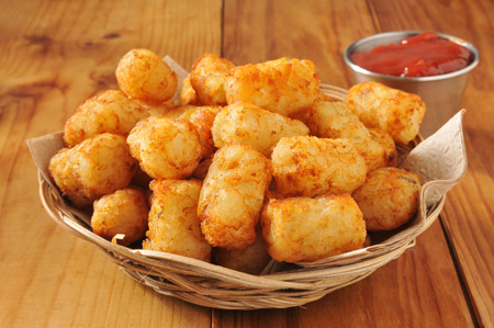 tots: A basket of tater tots on a rustic wooden counter