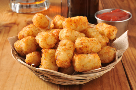 tots: A basket of golden tater tots with beer in the background
