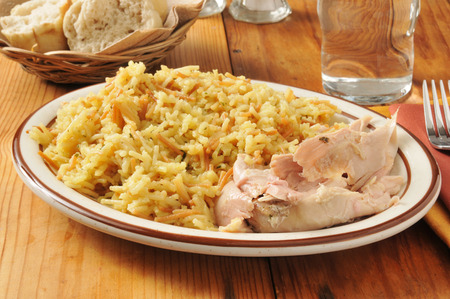 Chicken with rice and vermicelli served with dinner rolls Stock Photo