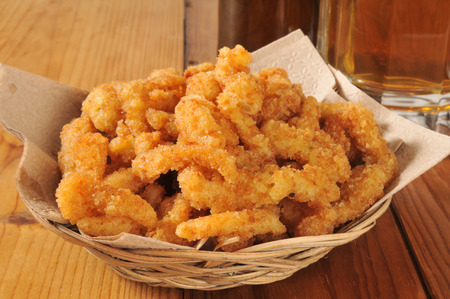 A basked of deep fried breaded clam strips with a mug of beer Stock Photo