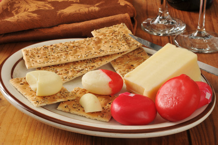 A wedge of asigo cheese with assorted cheeses in a red wax wrapper