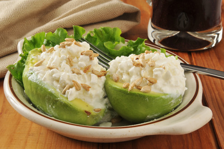 Avocado halves stuffed with cottage cheese and sunflower seeds