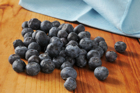 Fresh washed blueberries drying on a rustic wooden counter