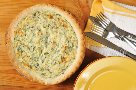 florentine: quiche florentine cooling near serving plates on rustic wooden table.  High angle view