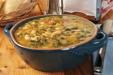 A healthy white bean and kale soup with dinner rolls
