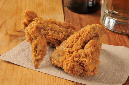 Fried chicken wings on a bar napkin with a mug of beef photo