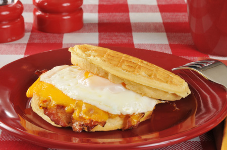 A bacon egg and American cheese sandwich on a waffle photo