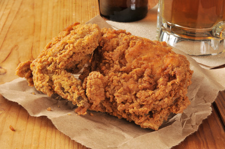 Fried chicken served on brown wrapping paper with a mug of beer on a bar counter photo