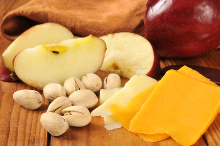 Sliced cheddar cheeses with apples and pistachio nuts Imagens