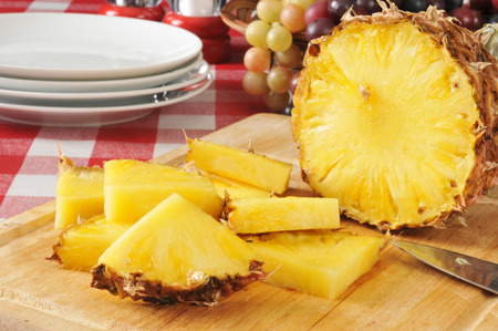 Sliced pineapple on a cutting board with a basket of fruit on a picnic table