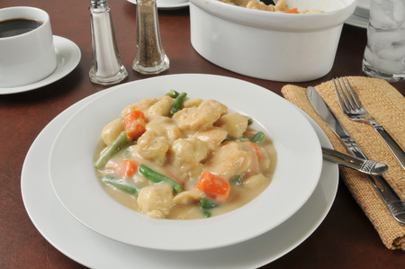 A bowl of chicken and dumplings with a casserole dish Imagens