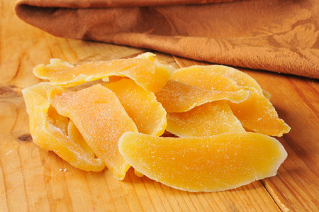 Dried mango or papaya slices on a wooden table Imagens