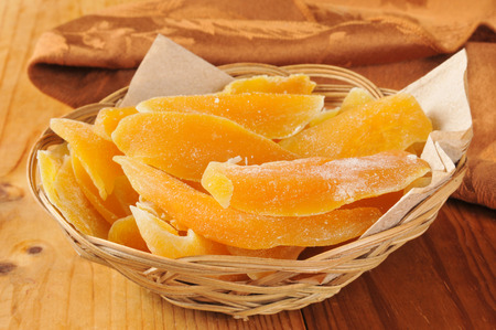 A basket of dried mango slices on a wooden table