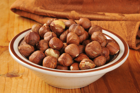 A small bowl of hazelnuts on a rustic wooden table