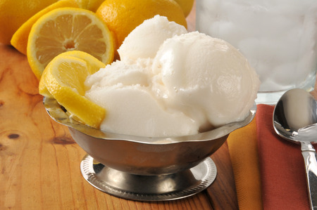 A silver serving dish of lemon sorbet on a wooden table