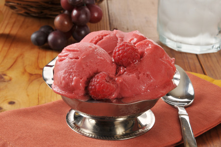 A silver serving dish of raspberry sorbet or sherbet on a wooden table