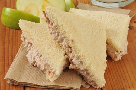 tunafish: A tunafish sandwich with the crust cut off and a sliced apple