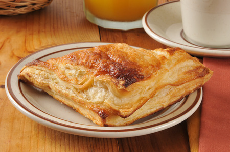 turnover: golden flaky apple turnover with orange juice and coffee Stock Photo
