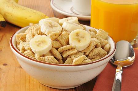 A bowl of cold rice breakfast cereal with sliced banana on top