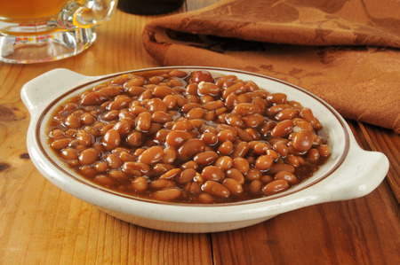 A bowl of baked beans in brown sugar sauce with a mug of beer photo