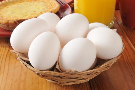 Una cesta de huevos frescos de granja con una quiche casero en el fondo Foto de archivo - 29623011