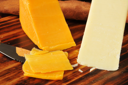 Wedges of white and yellow cheddar cheeses on a cutting board
