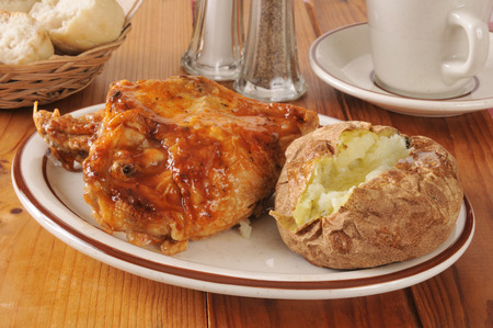 Barbecued chicken and a baked potato with dinner rolls