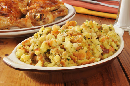 A bowl of corn bread stuffing with rotisserie chicken in the background