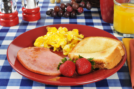 Ham and scrambled eggs with toast on a picnic table photo