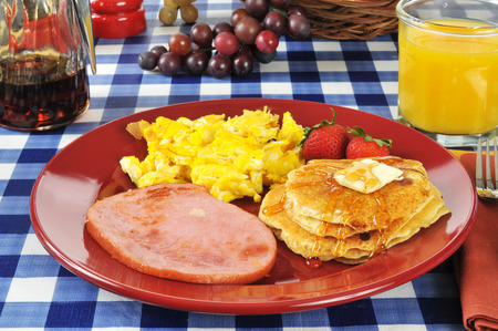 a ham and egg breakfast with pancakes on a picnic table photo