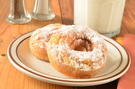 caked: Caked donuts with powdered sugar and a glass of milk Stock Photo