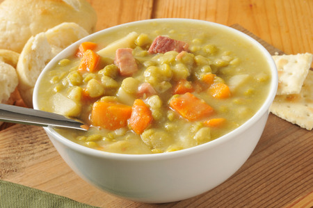 Split pea soup with ham, carrots and potatoes on a rustic wooden counter