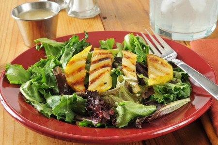 A grilled pear salad on a rustic wooden table