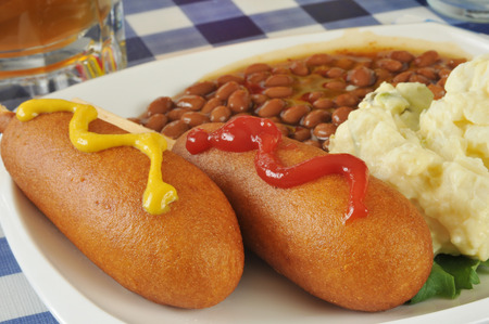 catsup: Close up of corn dogs with catsup and mustard