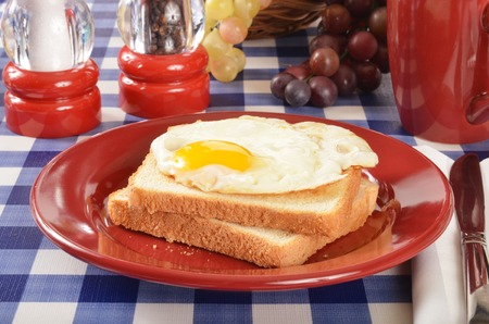 A fried egg sandwich on a picnic table with coffee photo