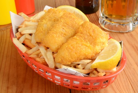 newsprint: Fish and chips served in a basket wrapped in newsprint with a mug of beer Stock Photo