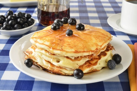 Blueberry pancakes on a picnic table with a cup of coffee photo